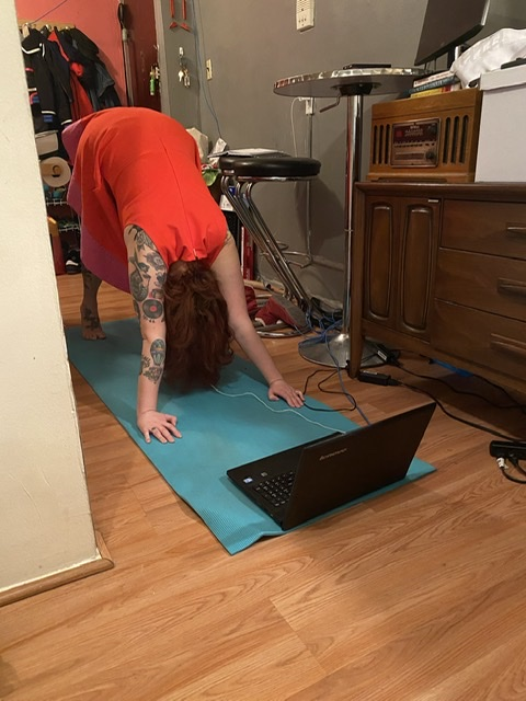 librarian in red dress with long hair performing a downward dog on a yoga mat, in front of their laptop