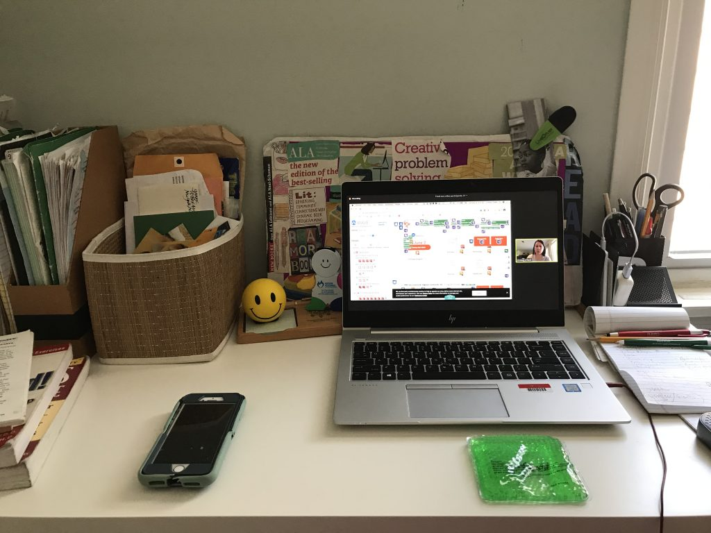 Desk with a phone, papers, and laptop on it, with a minimized webinar and calendar on the laptop screen.