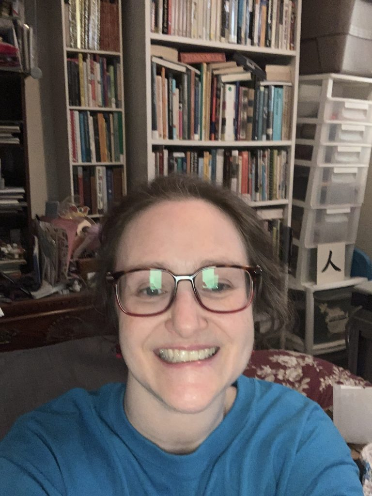 smiling librarian in front of a shelf of books